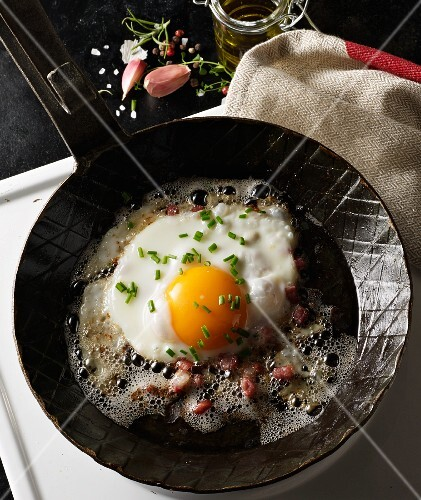 A fried egg with diced bacon and chives in a hot, black pan