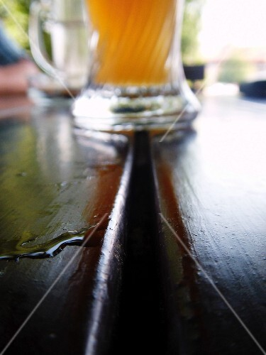 A glass of lager and drops of water on a wooden table