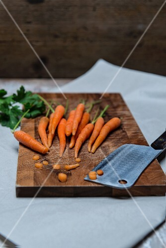 Carrots and parsley with a meat cleaver on a chopping board