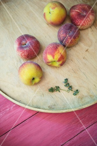 Peaches and thyme on a wooden surface