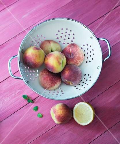 Peaches and vineyard peaches in a colander with mint and lemon