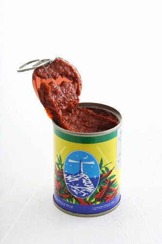 An opened tin of harissa sauce