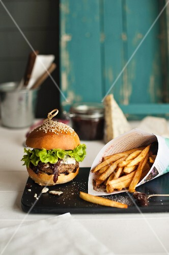 A hamburger with fries and onion relish
