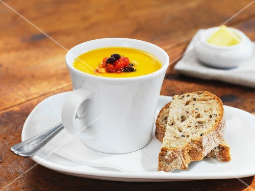Cream of pumpkin soup in a cup with bread