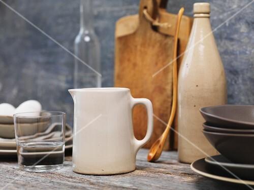 An arrangement featuring a job, a glass of water and other kitchen utensils