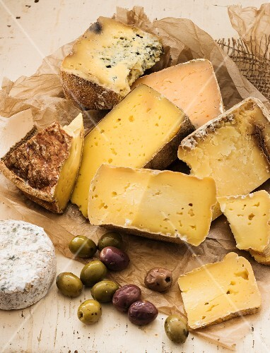 A selection of cheeses and olives on a wooden table