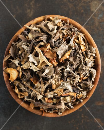 Dried mushrooms in a wooden bowl (seen from above)