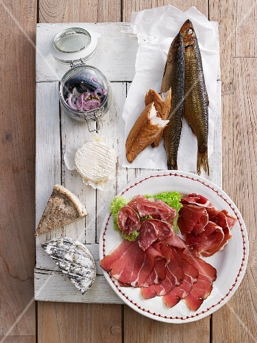 A plate of cold cuts featuring salami, raw ham, smoked fish and cheese for brunch