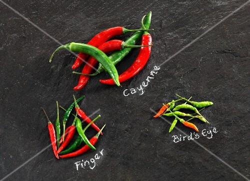 Various chilli peppers on a slate surface