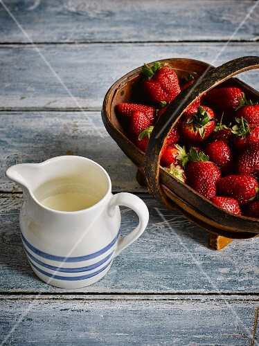 Fresh strawberries in a basket next to a jug of milk