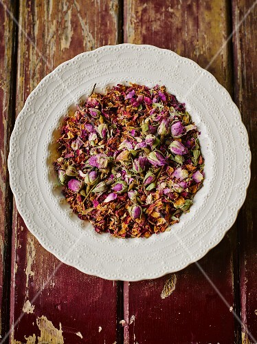 Dried rose buds and petals on a plate (seen from above)