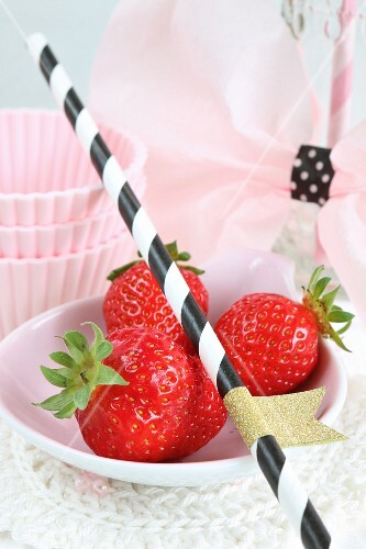 An arrangement of fresh strawberries, a straw and cake cases