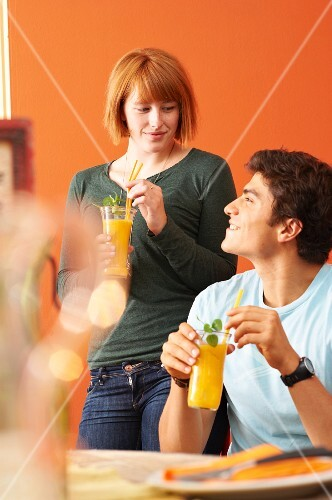 A young couple with mango mojitos