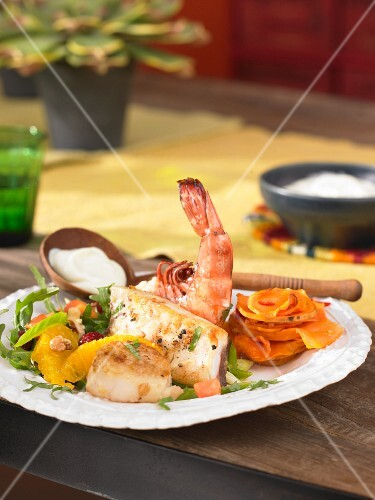 A seafood platter with a wasabi dip and a papaya salad