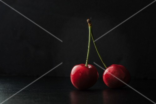 Two cherries on a black surface