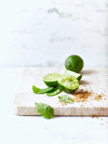 Limes, brown sugar and mint leaves for making mojitos