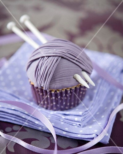 A ball of wool cupcake decorated with a knitting needles