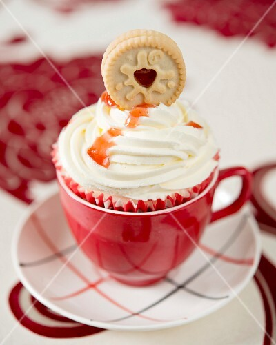 A cupcake decorated with a Jammy Dodger biscuit and strawberry jam