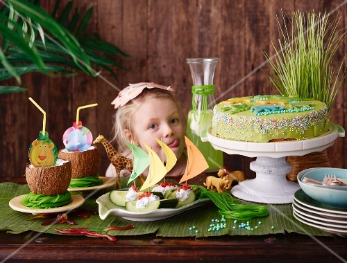 A little girl looking at a jungle party buffet