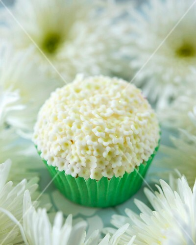 An elderflower cupcake with white fondant flowers