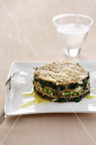 Spicy pancake cake with spinach, peas, mushrooms and cheese