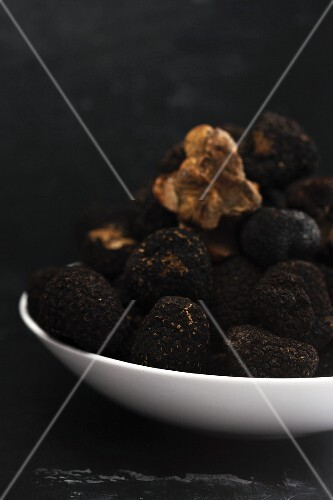 Black truffles on a white plate