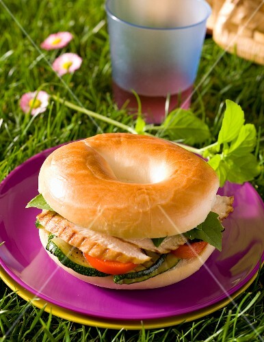A bagel with chicken breast, courgette and tomatoes on a plate in the grass
