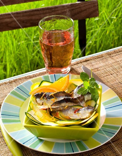Sardines with saffron and courgette strips on a table outside