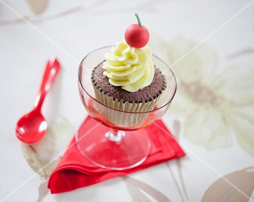 A chocolate cupcake decorated with a fondant cherry