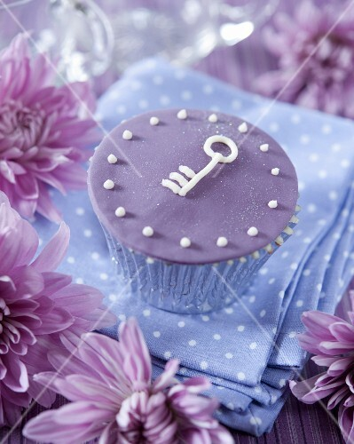 A purple cupcake decorated with a key