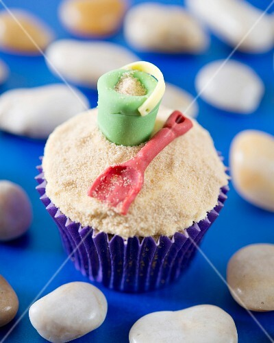A beach cupcake decorated with bucket and spade