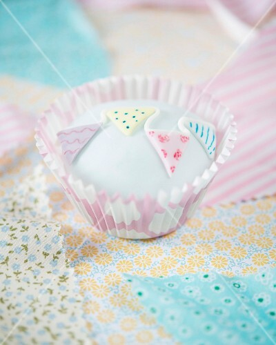 A cupcake decorated with fondant bunting