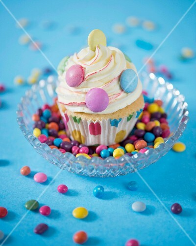 A cupcake decorated with vanilla butter cream and colourful chocolate beans