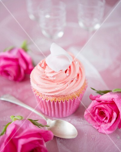 A cupcake decorated with rose petals