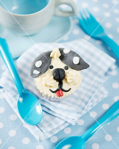 A cupcake decorated with a fondant dog face