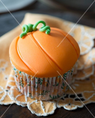 A pumpkin and cinnamon cupcake decorated with fondant icing for Halloween