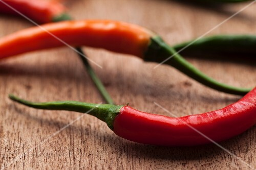 Fresh red chilli peppers on a wooden surface