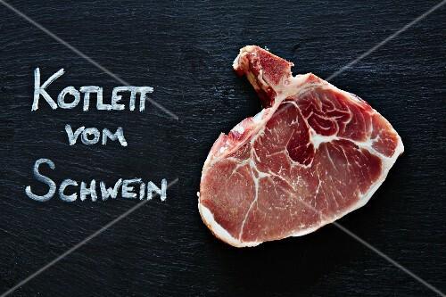 A raw pork chop with German writting