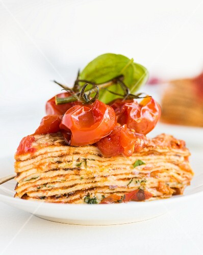 A slice of pancake cake with tomatoes