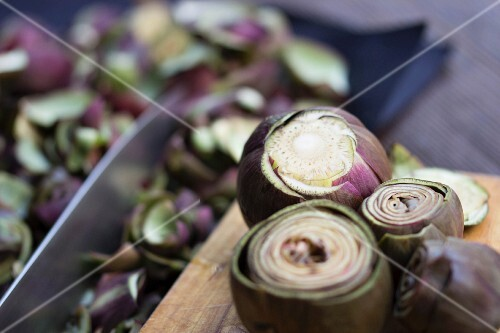 Fresh artichokes for preserving on a wooden board with a knife