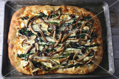 Pan pizza with mushrooms and spinach on a baking tray