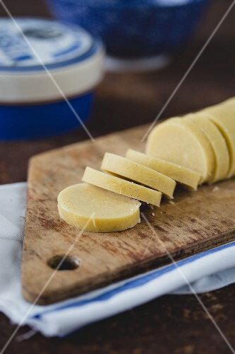 Vanilla butter biscuits being made: a roll of pastry being sliced