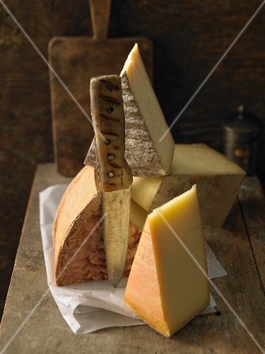 Various types of cheese on a wooden board with a knife