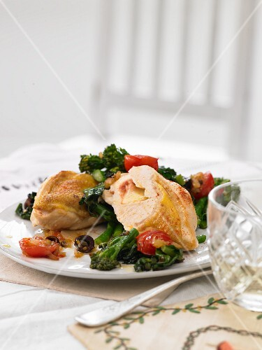 Cheese-filled corn-fed chicken on rapini with cherry tomatoes and olives