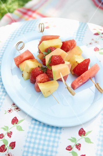 Colourful fruit skewers on a plate in a garden