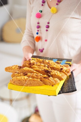 A woman serving BBQ focaccia with nuts and Cheddar cheese