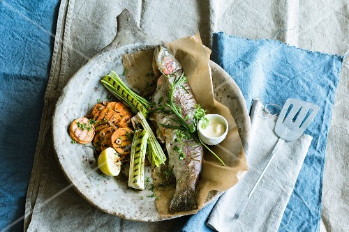 A whole grilled trout with sweet potatoes