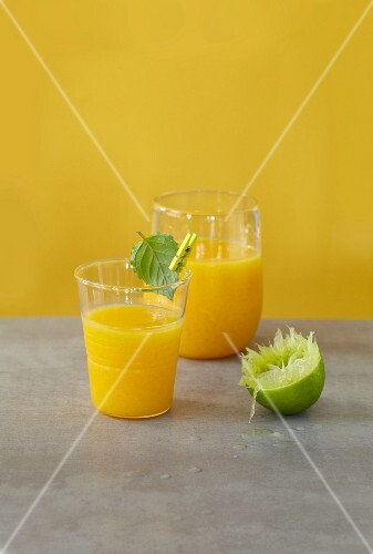 A ginger and mango smoothie with a juice lime and a mint leaf