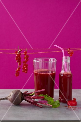 Beetroot juice with pomegranate, orange juice and sprigs of redcurrants
