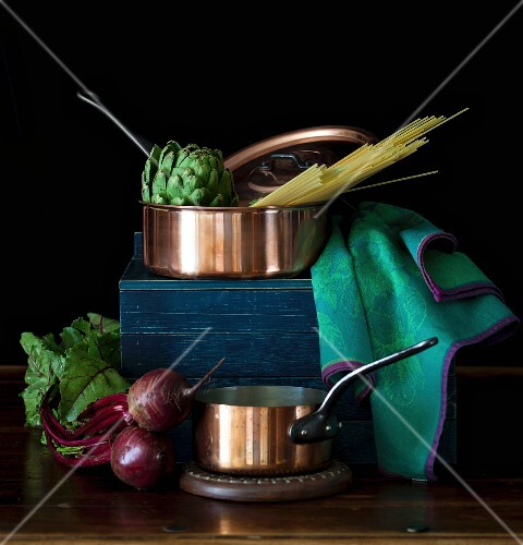 An arrangement of copper pans, vegetables and pasta